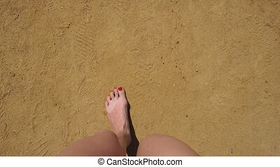 girl with red fingernails on her feet stepping on sand top...