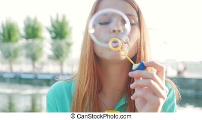 Girl with red hair blowing soap bubbles