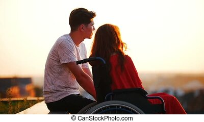 Girl With Red Hair Is Sitting In A Wheelchair And Boyfriend...