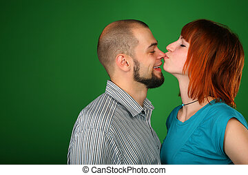 Girl with red hair kisses guy on nose