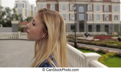 girl with red hair listens to music in the street