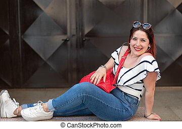 Girl with red hair lying on a bench