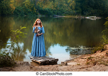 Girl with red hair standing on shore of the lake.
