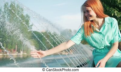 girl with red hair touches a hand stream of water from fountain, slow motion