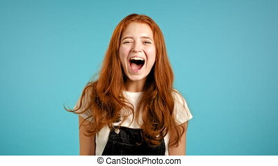 Girl with red hair very glad, she screaming loud. Woman trying to get attention. Concept of sales, profitable offer. Excited happy lady on blue studio background. High quality 4k footage