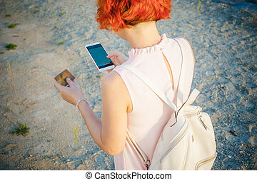 girl with red hair walking by the river at sunset, to make payments for online purchases from your device using a bank debit card. online payments, bank transfers.