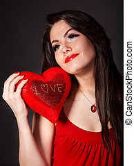 Girl with red heart on grey background.