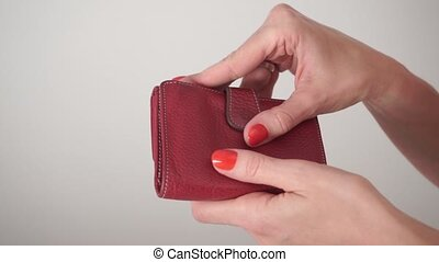 Girl with red nail polish opening her empty red purse