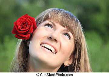 girl with red rose in hair looks upwards
