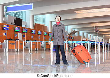 girl with red suitcase standing in airport hall