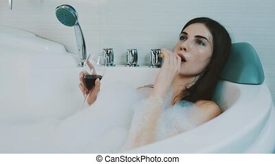 Girl with red wine glass in bath full of foam. Smoking electronic cigarette.
