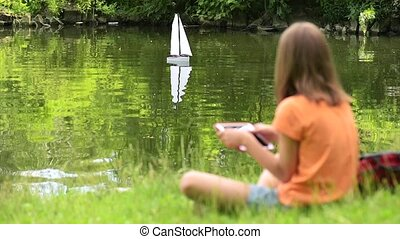 Girl with remote controlled boat