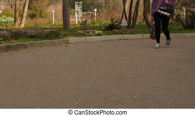 Girl With Roller-Skaters Is Walking In The Park