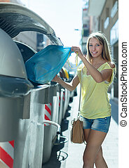 girl with rubbish near refuse container - girl with rubbish...