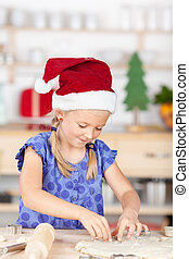 Girl with santas hat baking cookies