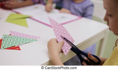 Girl with scissors cuts paper - Little girl with scissors...