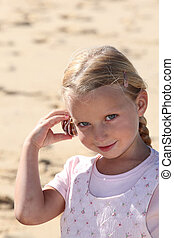 Girl with shell to ear