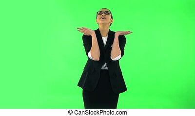 Girl with shocked wow face expression very rejoices. Green screen Girl with dark hair and glasses wearing a black business suit at green screen at studio.