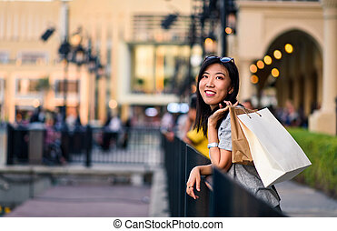 Girl with shopping bags in front of a mall