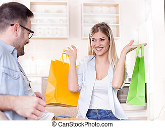 Girl with shopping bags in front of boyfriend