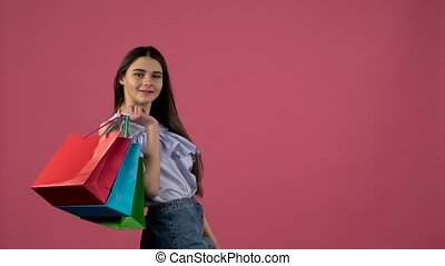 Girl with shopping bags with her back turning her head and...