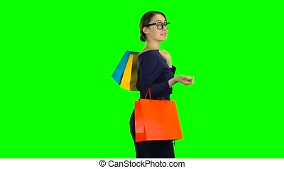 Girl with shopping packages in her hands is walking along...