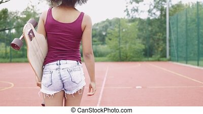 Girl with skateboard on sports ground - Back view of woman...