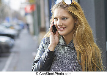 Girl with smartphone walking on city