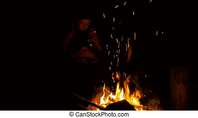 Girl with smartphones near the bonfire in the forest at night