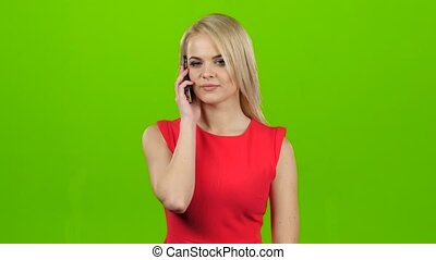 Girl with smile talking on mobile phone on green screen,...