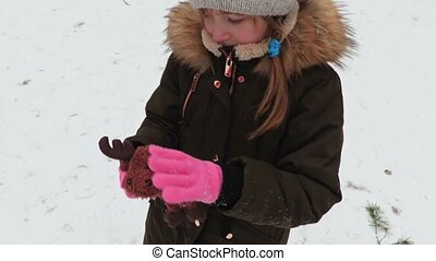 Girl with soft toy in winter