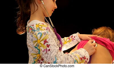 girl with stethoscope listens to his sister