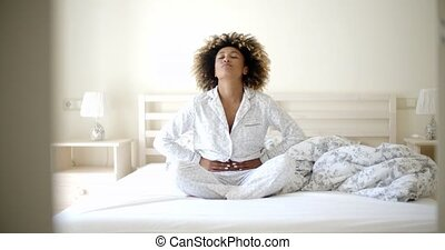 Girl With Stomach Ache Sitting On Bed