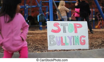 Girl With Stop Bullying Sign - A frightened little Asian...