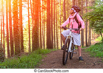 Girl with stops Mountain biking in the forest