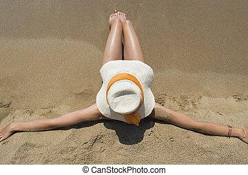 Girl with straw hat sitting on sandy beach