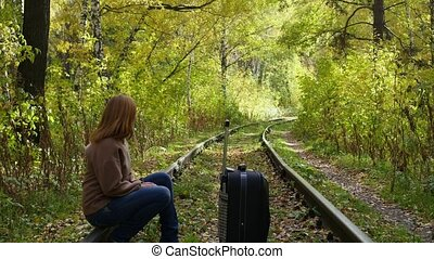 girl with suitcase walking along railroad