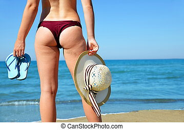 Girl with sun hat and flip flops on sunny tropical beach in bikinis.