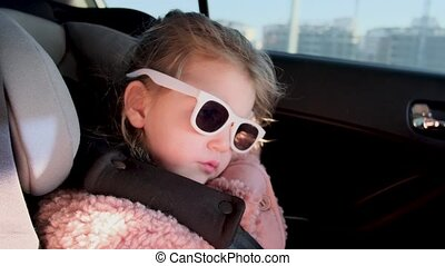 Adorable little girl with sunglasses and fluffy pink jacket sleeps in child safety seat riding on car along modern city street