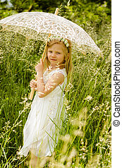 girl with long hair holding sunshade umbrella in green meadow