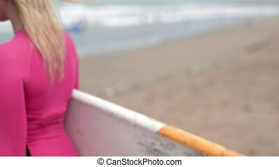 Girl with surfboard on beach - Glad blonde girl is walking...