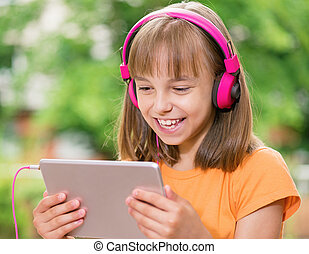 Girl with tablet and headphones