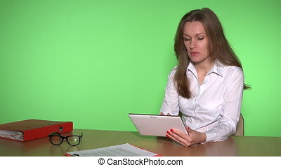girl with tablet computer in business meeting concept. Woman in white talking with partner. Green wall background. Static closeup shot. 4K UHD