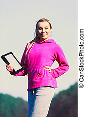 Girl with tablet in park.