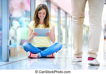 Girl with tablet in shopping mall