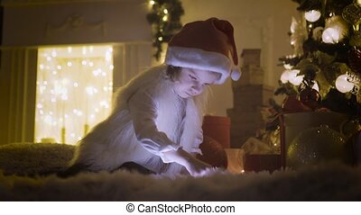 Girl with tablet near Christmas tree - Cute little girl in...