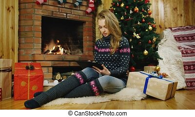 Girl with tablet near Christmas trees