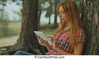 girl with tablet sitting against a tree in forest outdoors slow motion