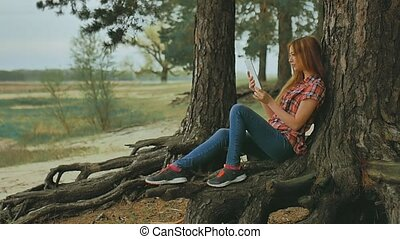 girl with tablet sitting against outdoors tree in forest slow motion