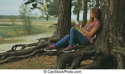 girl with tablet sitting against tree in forest slow motion outdoors